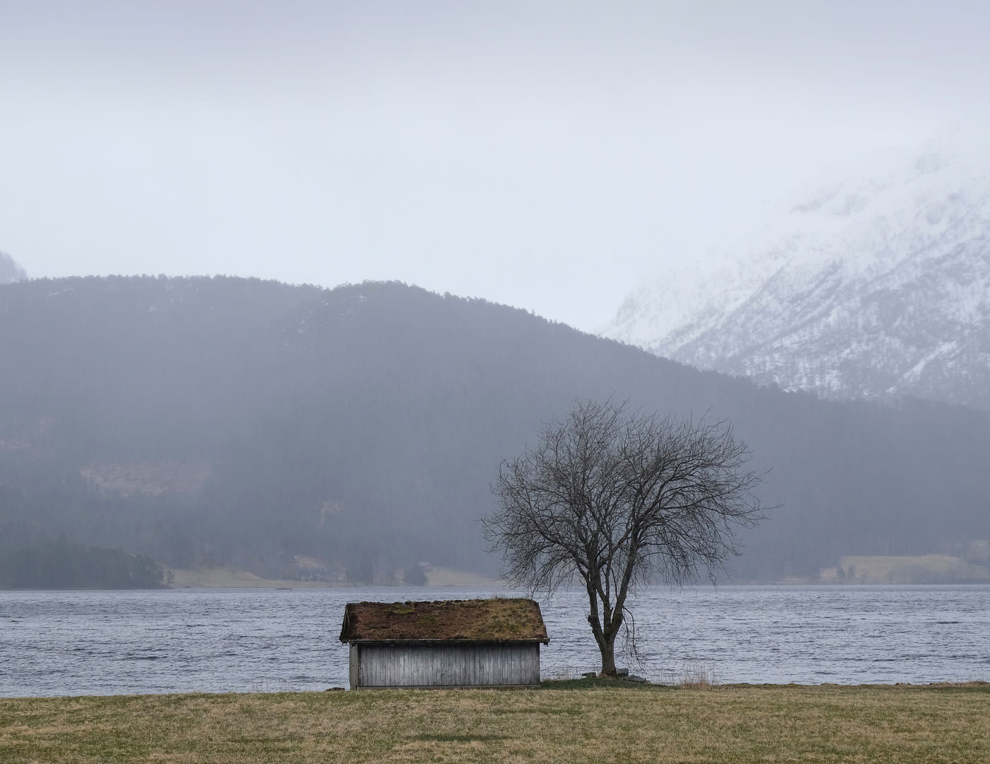 Cabin next to water and mountains